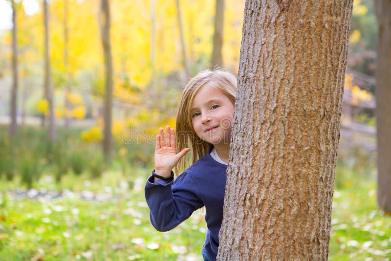 Το δάσος φθινοπώρου με το χαιρετισμό κοριτσιών παιδιών παραδίδει τον κορμό δέντρων στοκ φωτογραφία