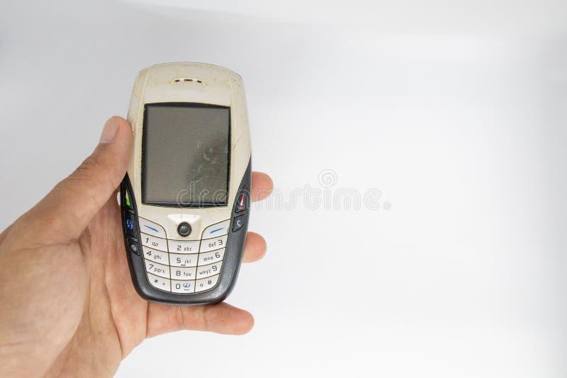 Το δάχτυλο που κρατά την παλαιά γενεά του κινητού τηλεφώνου με το λευκό απομονώνει το τεμαχισμένο υπόβαθρο στοκ φωτογραφία
