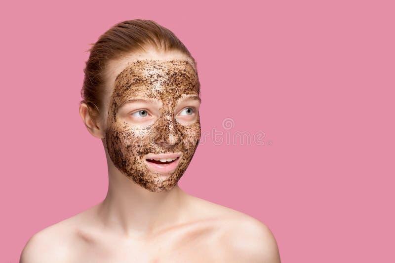 Το δέρμα προσώπου τρίβει Το πορτρέτο του προκλητικού θηλυκού προτύπου χαμόγελου που εφαρμόζει τη φυσική μάσκα καφέ, πρόσωπο τρίβε στοκ φωτογραφίες με δικαίωμα ελεύθερης χρήσης