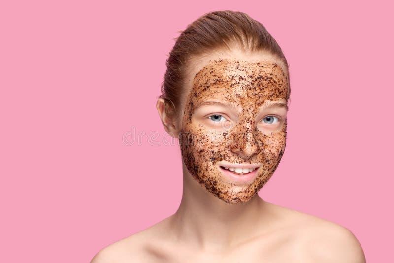 Το δέρμα προσώπου τρίβει Το πορτρέτο του προκλητικού θηλυκού προτύπου χαμόγελου που εφαρμόζει τη φυσική μάσκα καφέ, πρόσωπο τρίβε στοκ φωτογραφία