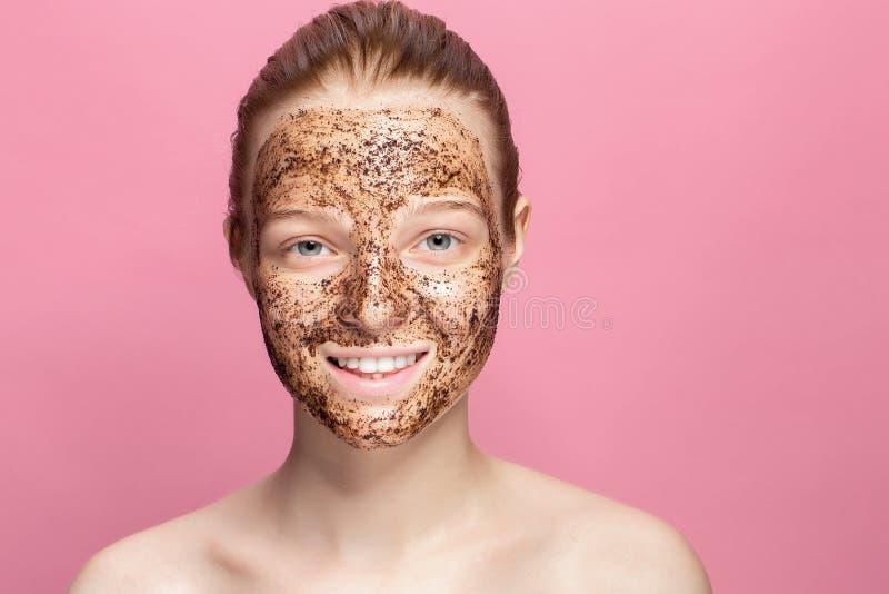 Το δέρμα προσώπου τρίβει Το πορτρέτο του προκλητικού θηλυκού προτύπου χαμόγελου που εφαρμόζει τη φυσική μάσκα καφέ, πρόσωπο τρίβε στοκ εικόνα με δικαίωμα ελεύθερης χρήσης