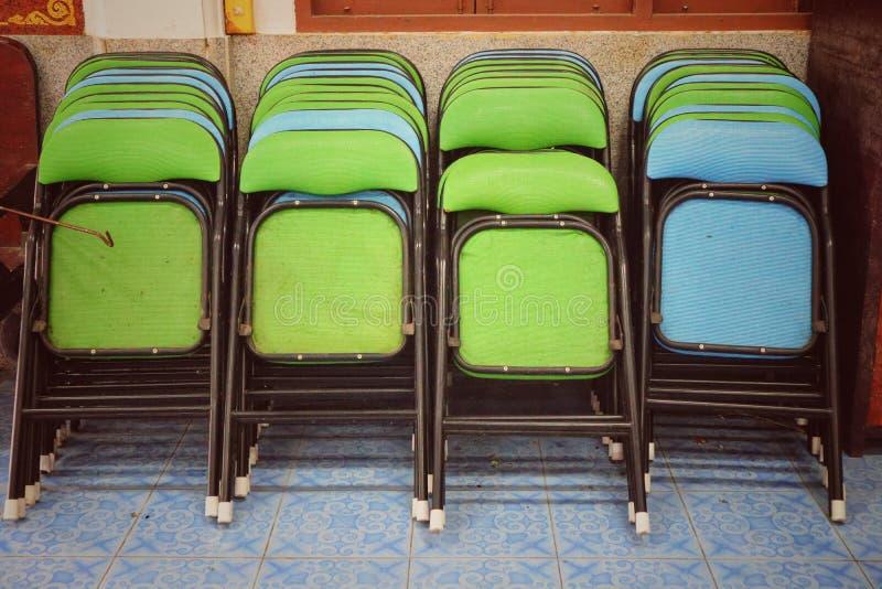 Το δίπλωμα των καρεκλών, παλαιός σίδηρος, πράσινος και μπλε, εκλεκτής ποιότητας ύφος, δίπλωσε σε μεγάλη ποσότητα στοκ εικόνες