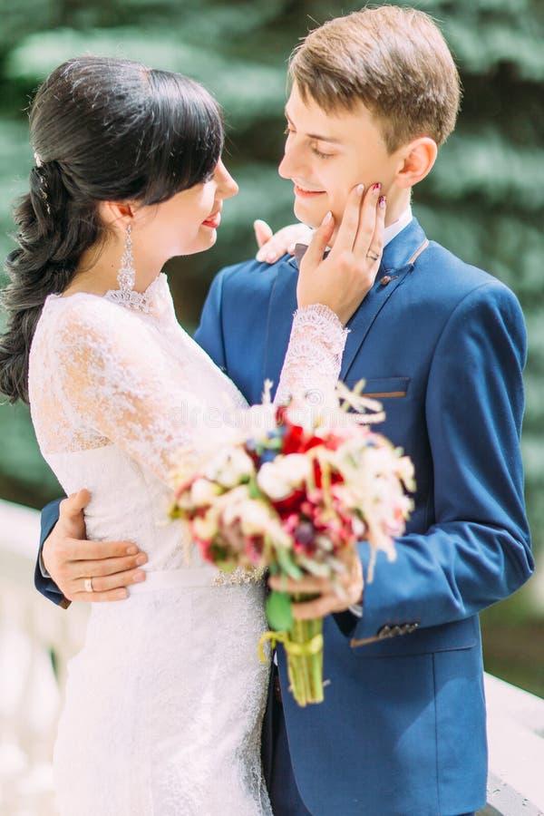 Το δευτερεύον πορτρέτο κινηματογραφήσεων σε πρώτο πλάνο της νύφης που κτυπά το μάγουλο του νεόνυμφου στοκ φωτογραφίες με δικαίωμα ελεύθερης χρήσης