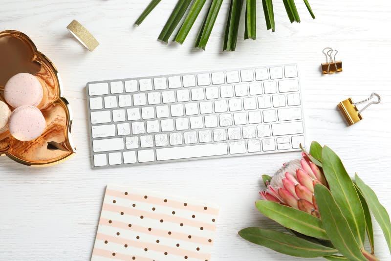 Το δημιουργικό επίπεδο βάζει τη σύνθεση με το τροπικά λουλούδι, macaroons και το πληκτρολόγιο υπολογιστών στοκ φωτογραφία