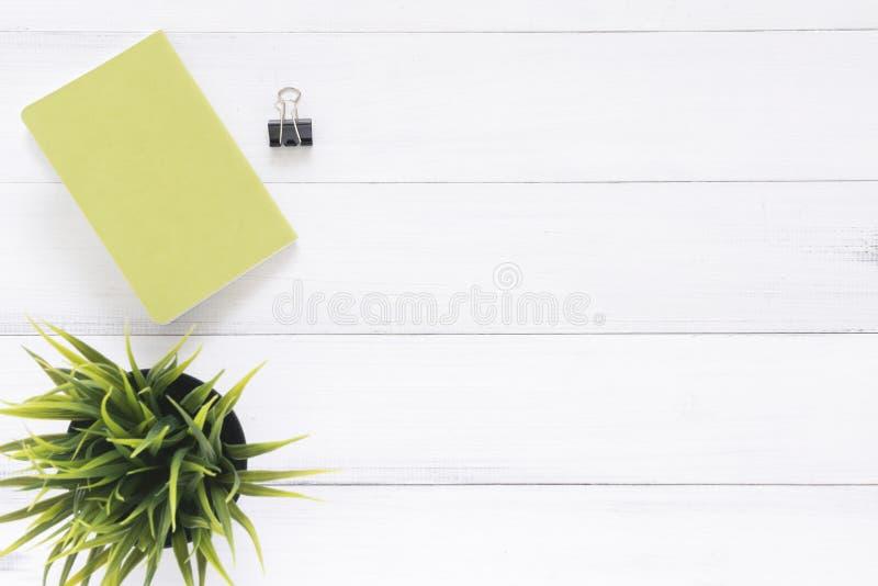 Το δημιουργικό επίπεδο βάζει τη φωτογραφία του γραφείου χώρου εργασίας Άσπρο ξύλινο επιτραπέζιο υπόβαθρο γραφείων γραφείων με τη  στοκ εικόνες