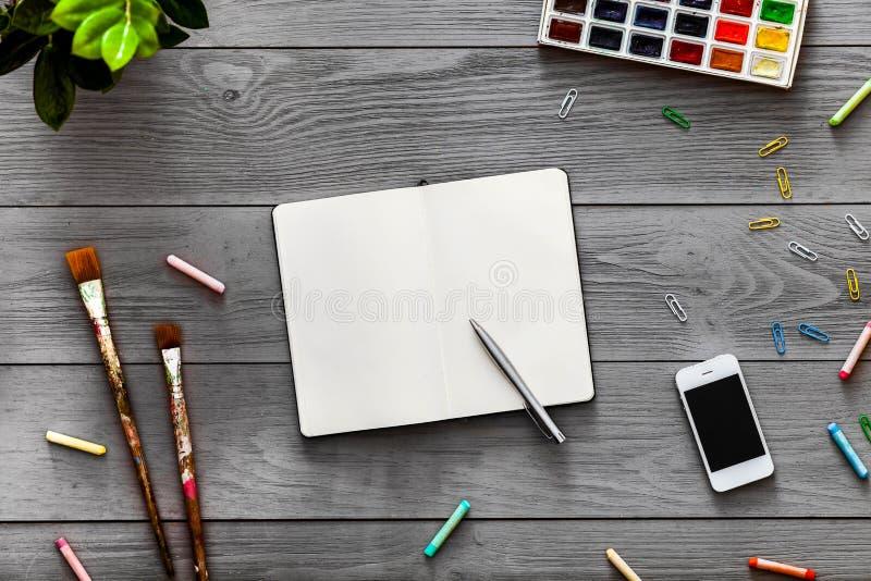 Το δημιουργικό επιτραπέζιο υπόβαθρο τέχνης με τα χρώματα σημειωματάριων, που σύρουν την εκπαίδευση, επίπεδο βρέθηκε στοκ εικόνα
