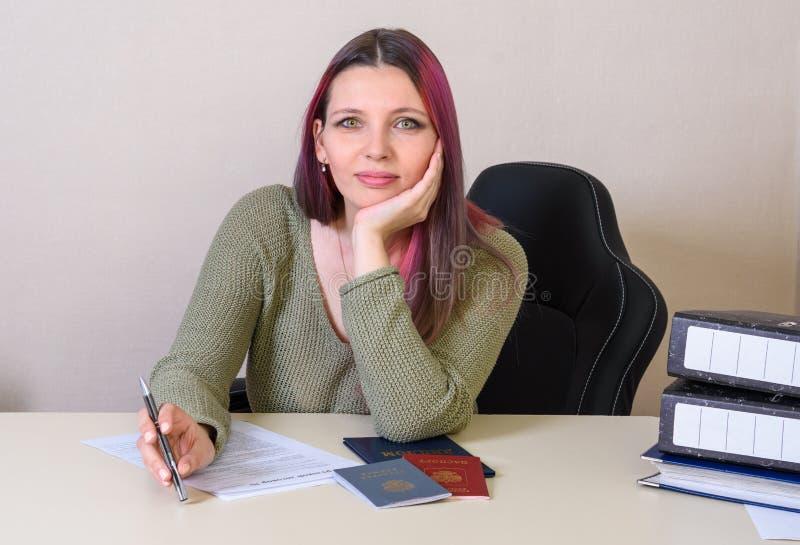 το δημιουργικό κορίτσι συμπληρώνει μια σύμβαση απασχόλησης και ένα αρχείο απασχόλησης, το διαβατήριο και το δίπλωμα στον πίνακα στοκ φωτογραφίες με δικαίωμα ελεύθερης χρήσης