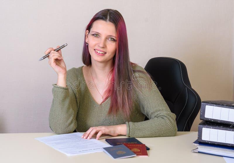 το δημιουργικό κορίτσι συμπληρώνει μια σύμβαση απασχόλησης και ένα αρχείο απασχόλησης, το διαβατήριο και το δίπλωμα στον πίνακα στοκ φωτογραφίες