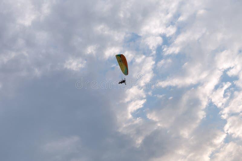 Το διαδοχικό ανεμόπτερο μηχανών πετά μέσω ενός όμορφου νεφελώδους ουρανού βραδιού με έναν πειραματικό και έναν επιβάτη στοκ φωτογραφία