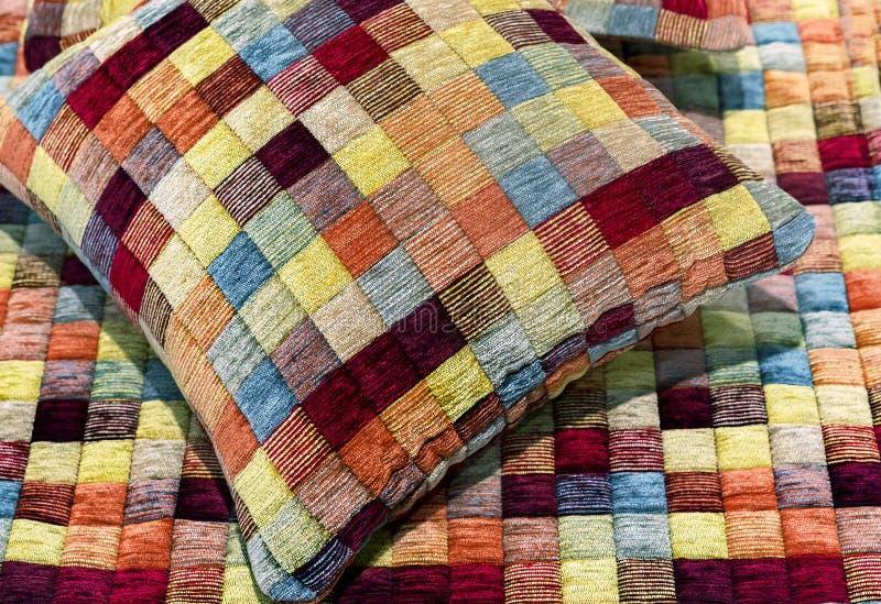 Το διακοσμητικά μαξιλάρι και το καρό ράβονται από τα πολύχρωμα κομμάτια του υφάσματος στοκ φωτογραφία με δικαίωμα ελεύθερης χρήσης