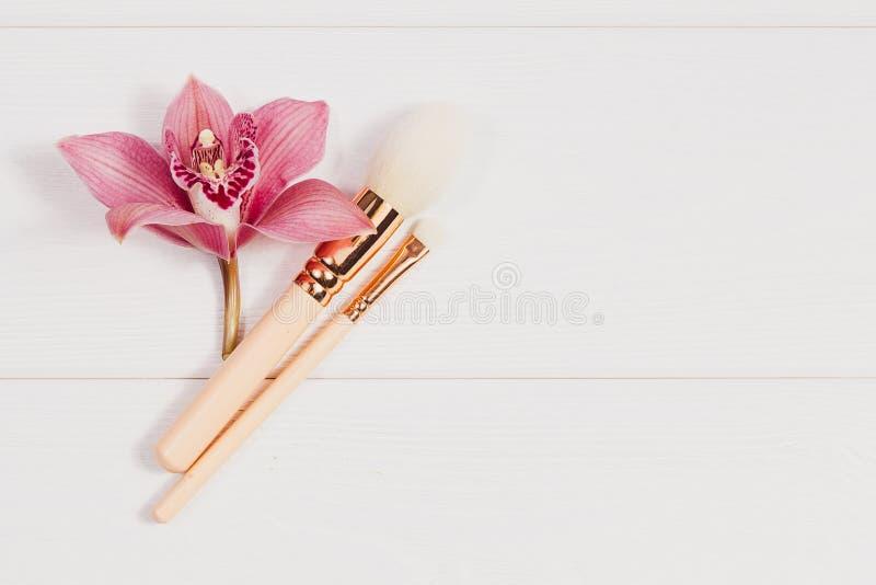 Το διακοσμητικό επίπεδο βάζει τη σύνθεση με τα προϊόντα και τα λουλούδια makeup Επίπεδος βάλτε, τοπ άποψη σχετικά με το άσπρο υπό στοκ φωτογραφίες με δικαίωμα ελεύθερης χρήσης