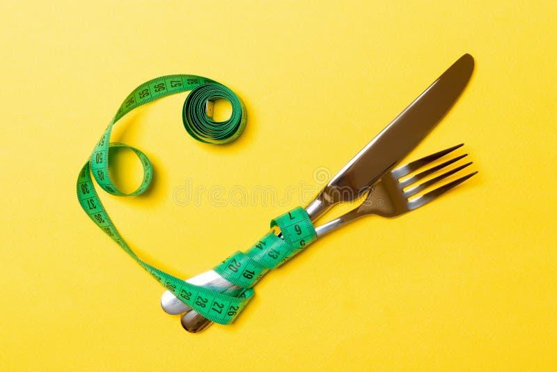 Το διασχισμένα δίκρανο και το μαχαίρι είναι τυλιγμένα στη μέτρηση της ταινίας στο κίτρινο υπόβαθρο Έννοια της διατροφής για την α στοκ εικόνες
