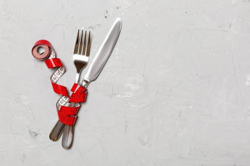 Το διασχισμένα δίκρανο και το μαχαίρι είναι τυλιγμένα στη μέτρηση της ταινίας στο γκρίζο υπόβαθρο Έννοια της διατροφής για την απ στοκ εικόνα