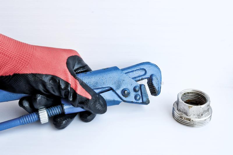 Το διευθετήσιμο γαλλικό κλειδί αερίου σε έναν ανθρώπινο παραδίδει ένα κόκκινο λειτουργώντας γάντι Εργαλείο κλειδαράδων στοκ εικόνες