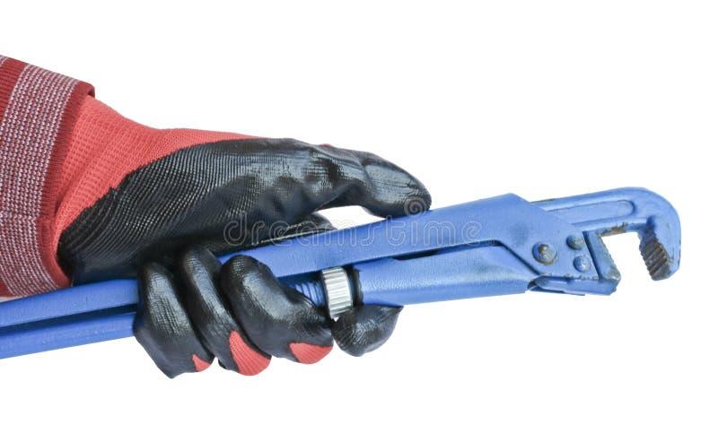 Το διευθετήσιμο γαλλικό κλειδί αερίου σε έναν ανθρώπινο παραδίδει ένα κόκκινο λειτουργώντας γάντι Εργαλείο κλειδαράδων στοκ φωτογραφία