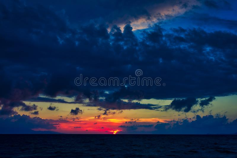 Το δραματικό cloudscape πέρα από το νερό, ηλιοβασίλεμα, ήλιος πήγε σχεδόν στη θάλασσα στοκ εικόνα