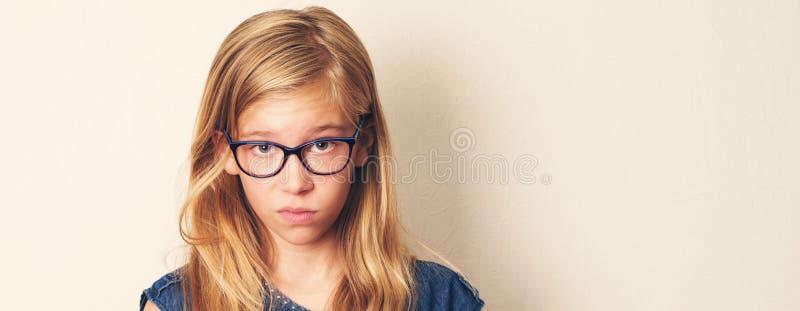 Το δυσαρεστημένο κορίτσι εφήβων κοιτάζει ύποπτα, δύσπιστος, φορώντας gl στοκ εικόνα