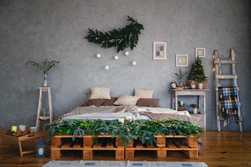 Το δωμάτιο σύγχρονου σχεδίου ύφους σοφιτών με ένα διπλό κρεβάτι στα ελαφριά χρώματα διακόσμησε για τις διακοπές Χριστουγέννων και στοκ εικόνες με δικαίωμα ελεύθερης χρήσης
