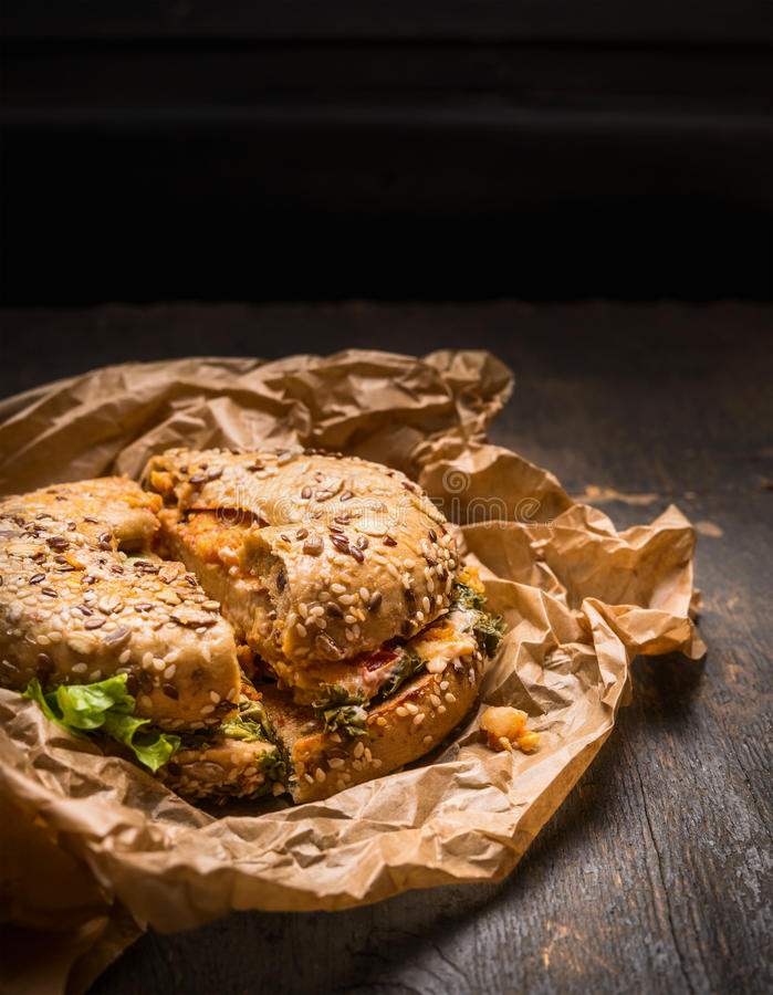 Το εγκάρδιο σάντουιτς προγευμάτων Bagel με και τα φύλλα και το τυρί σαλάτας στο αγροτικό ξύλινο υπόβαθρο, κλείνουν επάνω στοκ εικόνες
