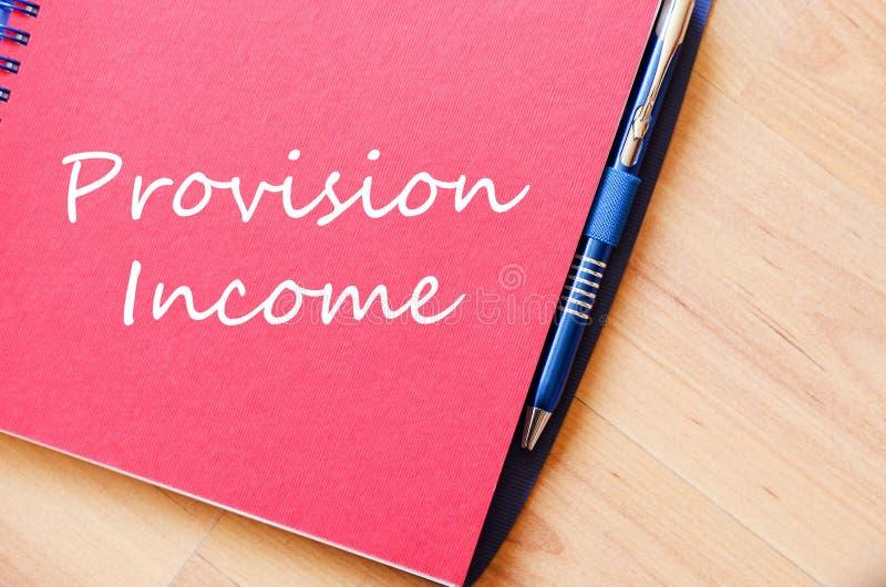 Το εισόδημα παροχής γράφει στο σημειωματάριο στοκ φωτογραφία