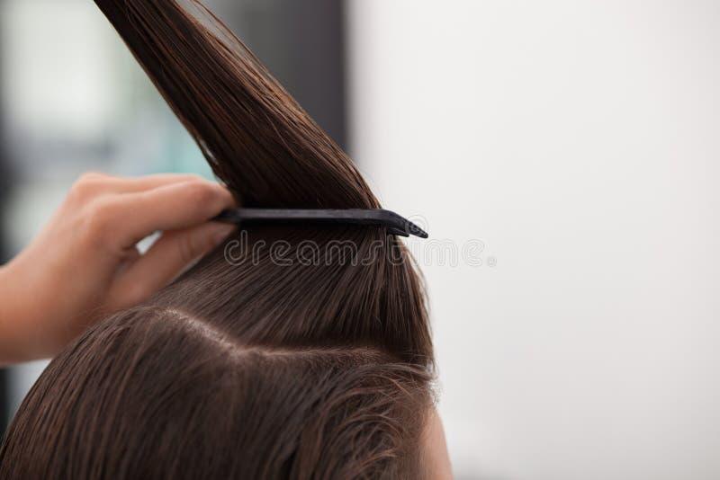Το ειδικευμένο νέο hairstylist εξυπηρετεί τον πελάτη της στοκ φωτογραφία