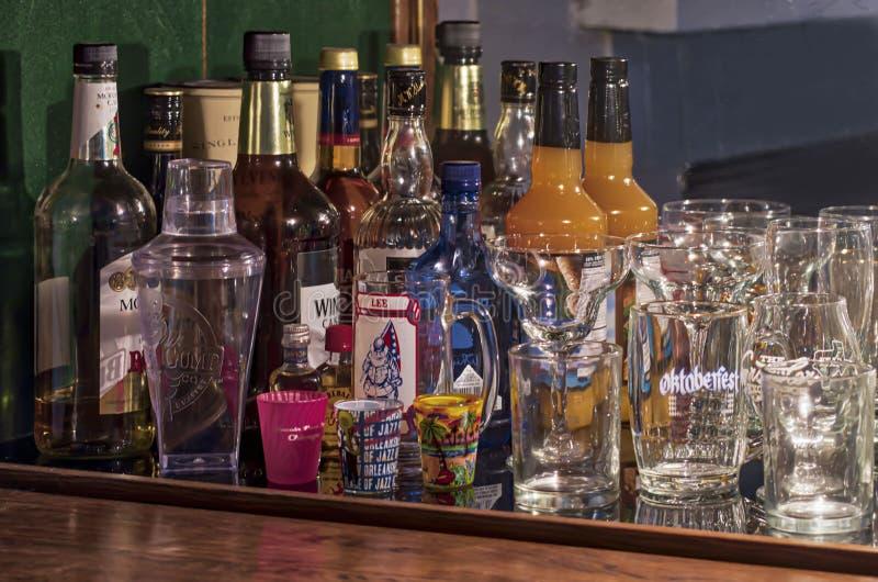 Το εκλεκτής ποιότητας γραφείο ποτού εφοδίασε με τα μπουκάλια και τα γυαλικά στοκ φωτογραφία