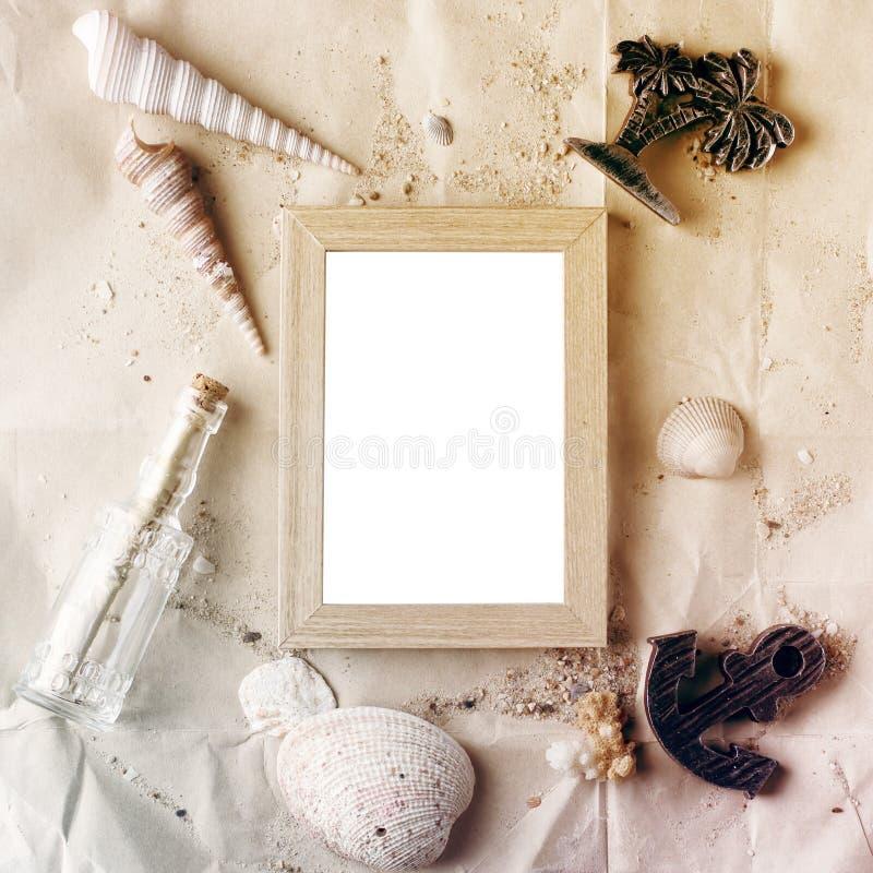 Το εκλεκτής ποιότητας ξύλινο πλαίσιο φωτογραφιών σε χαρτί τεχνών με τα κοχύλια άμμου και θάλασσας χλευάζει επάνω στοκ εικόνα