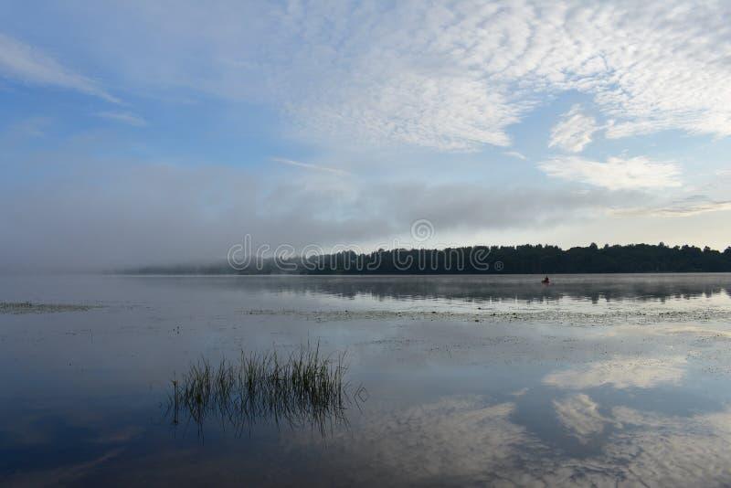 Το εκπληκτικά όμορφο πρωί αρχών του καλοκαιριού στον ποταμό, σύννεφα απεικόνισε στην επιφάνεια νερού στοκ εικόνα με δικαίωμα ελεύθερης χρήσης