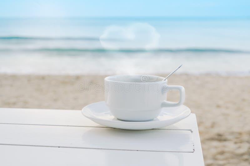 Το εκτυφλωτικό φλυτζάνι καφέ με την καρδιά διαμόρφωσε τον καπνό στο ξύλινο γραφείο κοντά στην παραλία το πρωί στοκ φωτογραφίες με δικαίωμα ελεύθερης χρήσης