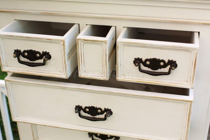 Το εκλεκτής ποιότητας ξύλινο στήθος των συρταριών με το μαύρο μέταλλο χειρίζεται ανοικτό στοκ φωτογραφίες