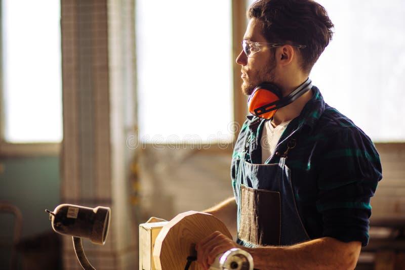 Το ελκυστικό άτομο αρχίζει την ξυλουργική στην ξυλουργική στοκ εικόνα με δικαίωμα ελεύθερης χρήσης