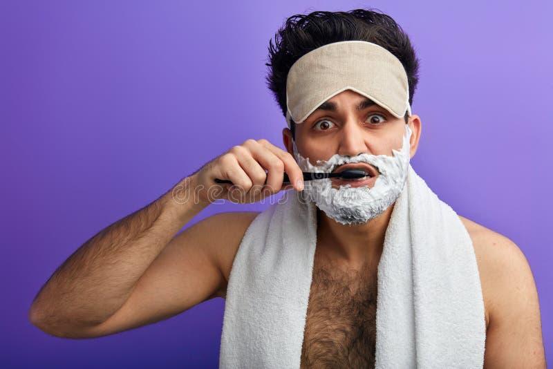 Το ελκυστικό άτομο με την κρέμα ξυρίσματος στο πρόσωπό του φροντίζει τα δόντια του στοκ εικόνες