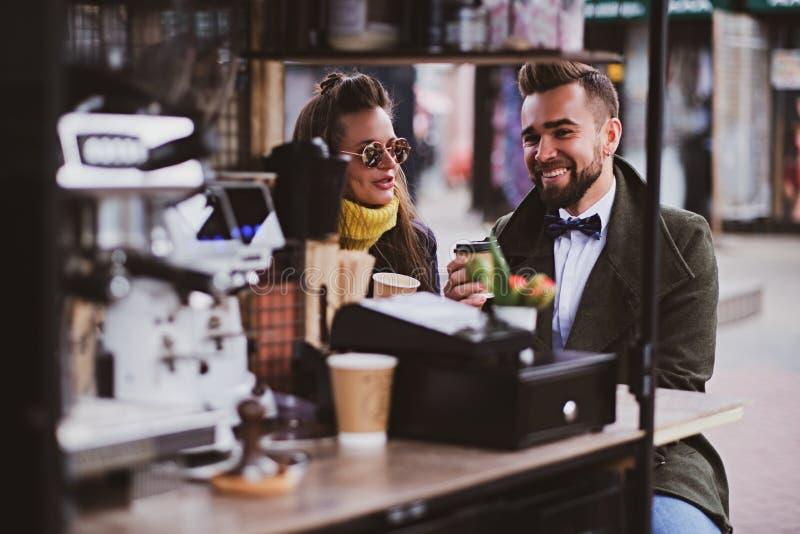 Το ελκυστικό έξυπνο ζεύγος απολαμβάνει τον καφέ καθμένος έξω στο μικρό coffeesho στοκ εικόνες