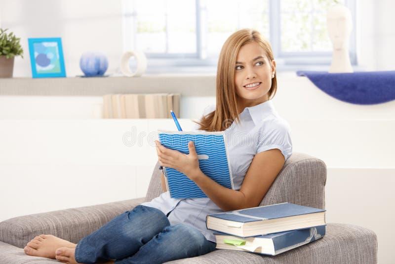 Το ελκυστικό γράψιμο κοριτσιών σημειώνει στο σπίτι να χαμογελάσει στοκ εικόνα με δικαίωμα ελεύθερης χρήσης