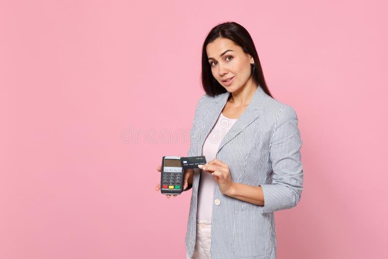 Το ελκυστικό γυναικών τερματικό πληρωμής τραπεζών λαβής ασύρματο σύγχρονο στη διαδικασία, αποκτά τις πληρωμές με πιστωτική κάρτα  στοκ εικόνες με δικαίωμα ελεύθερης χρήσης