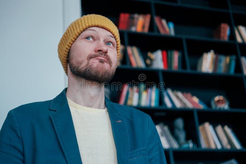 Το ελκυστικό ενήλικο γενειοφόρο άτομο hipster στο κίτρινο καπέλο φαίνεται επάνω και χαμογελά slyly στο υπόβαθρο τοίχων βιβλίων στοκ εικόνα