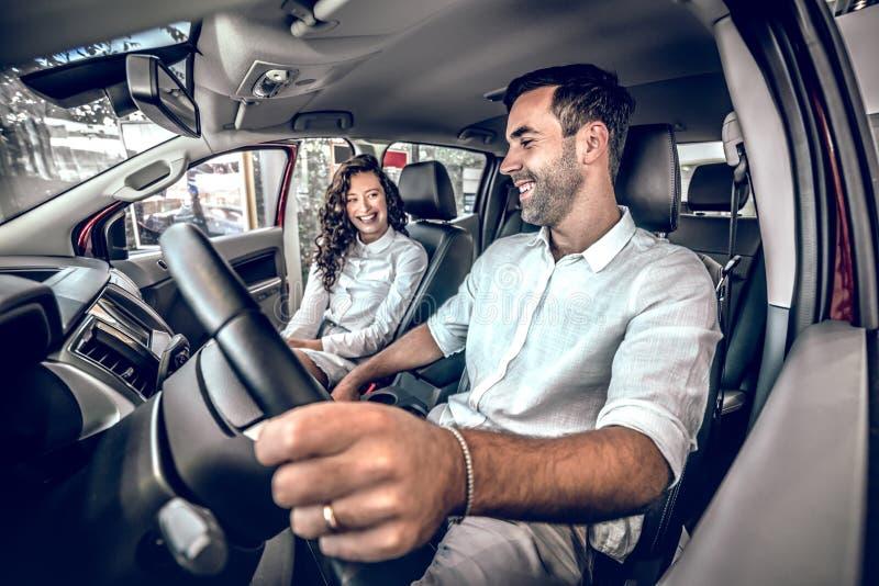 Το ελκυστικό ζεύγος επιλέγει ένα νέο αυτοκίνητο στην αίθουσα εκθέσεως στοκ φωτογραφίες