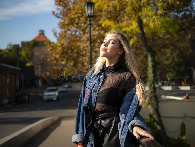 Το ελκυστικό κορίτσι με την όμορφη ρέοντας τρίχα έκλεισε τα μάτια της στο φωτεινό ήλιο στοκ φωτογραφία