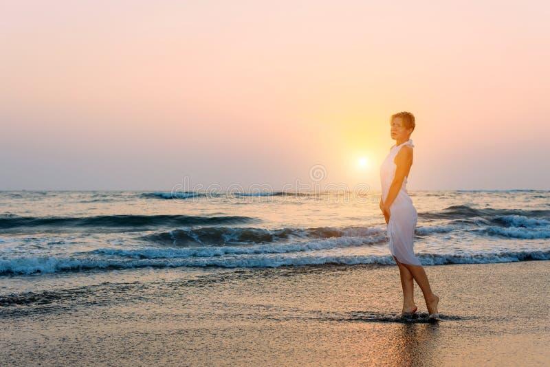 Το ελκυστικό λεπτό κορίτσι στο άσπρο φόρεμα στέκεται στα κύματα στη θάλασσα λαμβάνοντας υπόψη τη ρύθμιση του ήλιου Νέοι περίπατοι στοκ εικόνα