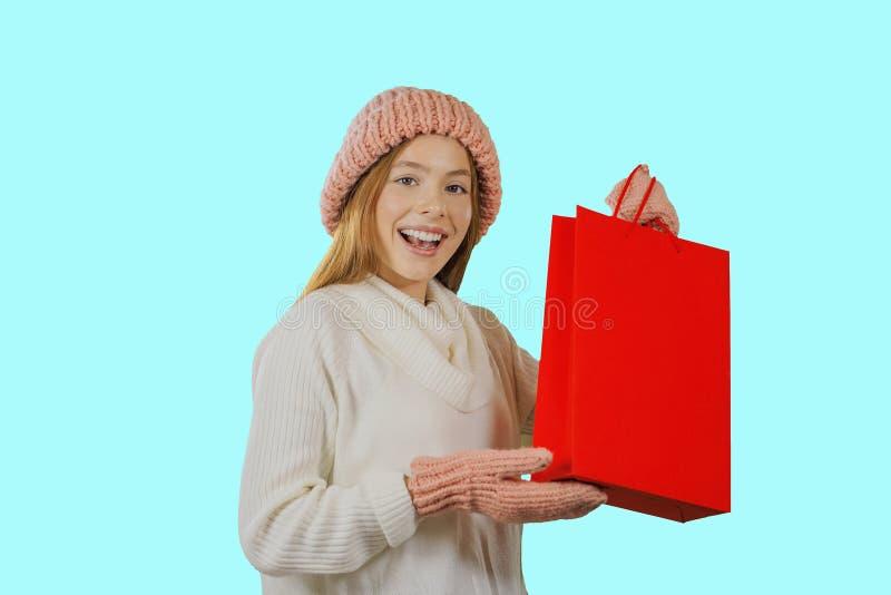 Το ελκυστικό νέο εύθυμο κοκκινομάλλες κορίτσι με ένα δώρο στα χέρια της εξετάζει τη κάμερα και χαμογελά απομονωμένη στοκ εικόνες