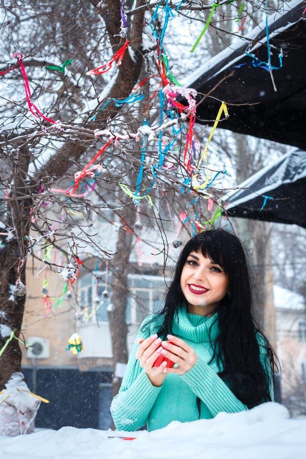 Το ελκυστικό νέο κορίτσι πίνει ένα coffe στον καφέ οδών στα χιονώδη WI στοκ εικόνες