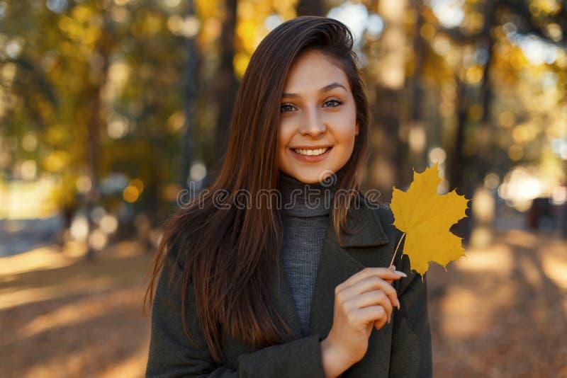 Το ελκυστικό όμορφο μοντέρνο ευτυχές κορίτσι με ένα χαμόγελο σε ένα μοντέρνο εκλεκτής ποιότητας πράσινο παλτό κρατά στο χέρι της  στοκ φωτογραφίες