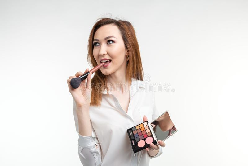 Το ελκυστικό visagist ή ο κορεατικός καλλιτέχνης σύνθεσης που κρατά ένα makeup βουρτσίζει και μια παλέτα της σκιάς ματιών στο άσπ στοκ φωτογραφίες