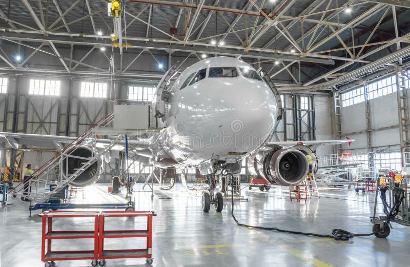 Το εμπορικό αεριωθούμενο αεροπλάνο αεροσκαφών στη συντήρηση της μηχανής και η άτρακτος ελέγχουν την επισκευή στο υπόστεγο αερολιμ στοκ εικόνες