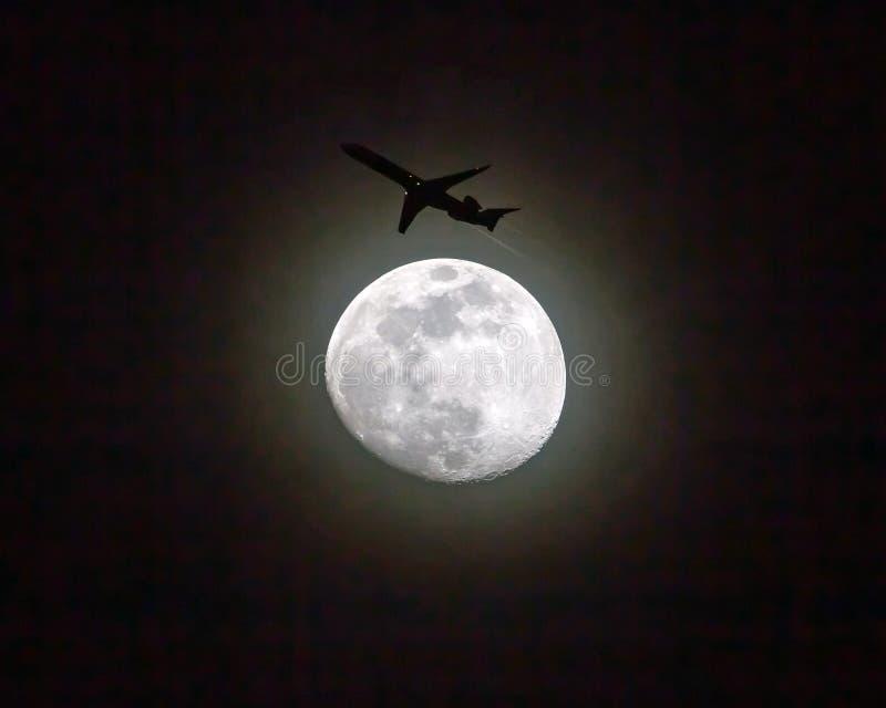 Το εμπορικό επιβατηγό αεροσκάφος περνά εδώ κοντά μια πανσέληνο τη νύχ στοκ εικόνα