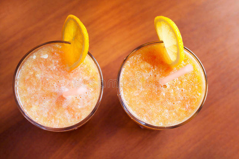 Το λεμόνι και οι πορτοκαλιοί καταφερτζήδες στον πίνακα με τις φέτες του λεμονιού και του πορτοκαλιού σε ένα γυαλί κοιλαίνουν με τ στοκ φωτογραφίες με δικαίωμα ελεύθερης χρήσης