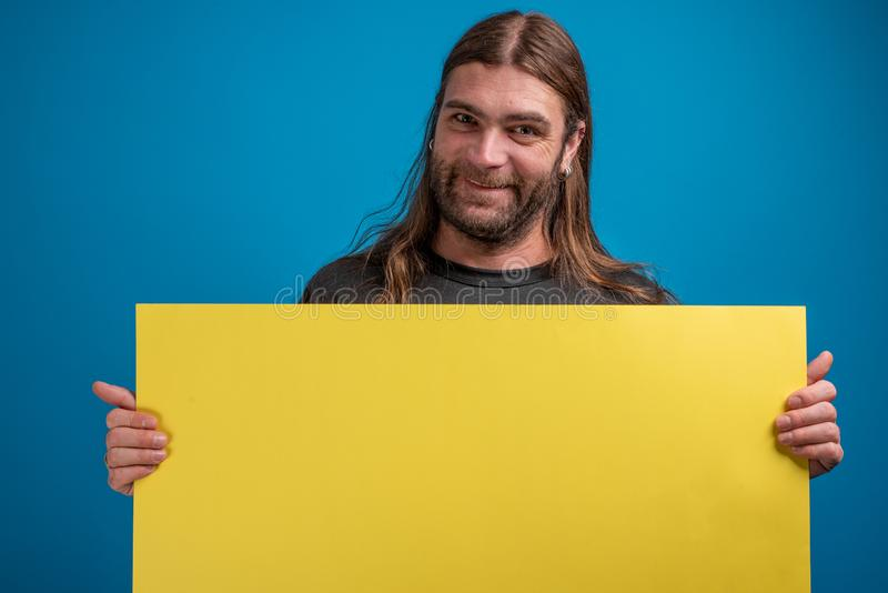 Το ενήλικο αρσενικό που κάνει τα αστεία πρόσωπα στη κάμερα κρατώντας ένα κίτρινο διαφημίζει το έμβλημα στοκ φωτογραφία με δικαίωμα ελεύθερης χρήσης