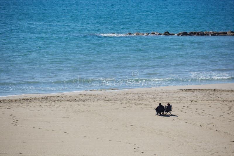 Το ενήλικο ζεύγος με τις καρέκλες εξετάζει την τυρκουάζ θάλασσα και απόλαυση της ηλιόλουστης ημέρας άνοιξη στην παραλία άμμου της στοκ φωτογραφία με δικαίωμα ελεύθερης χρήσης