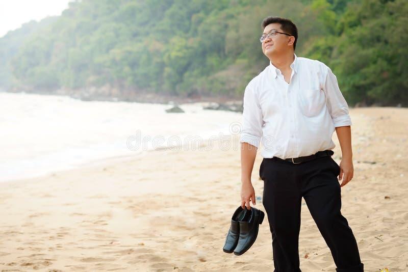 Το ενήλικο ασιατικό παχύ άτομο στο άσπρο πουκάμισο και φέρνει τα παπούτσια αισθαμένος ότι αποθαρρημένος από τη σκληρή δουλειά βρί στοκ εικόνες με δικαίωμα ελεύθερης χρήσης