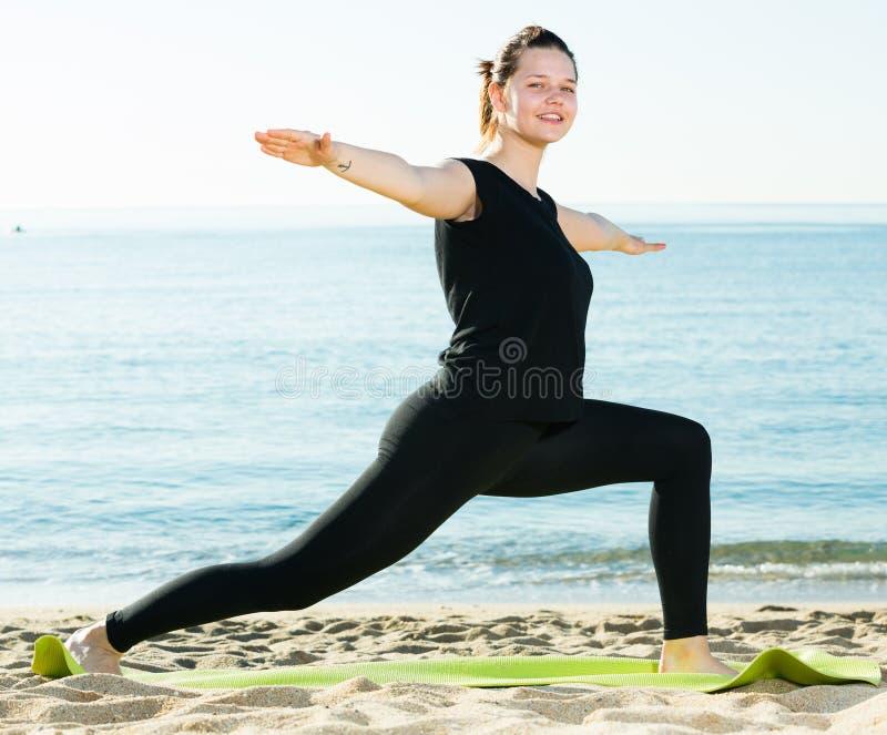Το ενήλικο θηλυκό στη μαύρη μπλούζα τεντώνει στοκ εικόνα